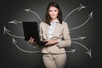 Business woman holding a laptop with arrows drawn behind her in multiple directions.