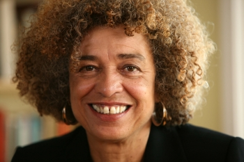 Headshot of Angela Davis smiling in a black blazer in front of a blurred bookcase background.