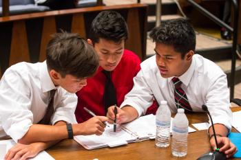 ASU APACE Academy students Marc Flom, 16, left, Dwayne Lanwe, 16, and Randy Oshiro, 15, right, plan strategy in the mock trial