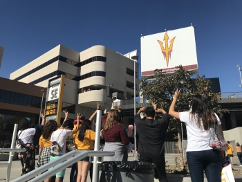 Foster youth with their backs turned giving Forks Up in front of Sun Devil Stadium