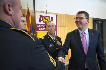 Secretary of Defense shaking hands with members of the military