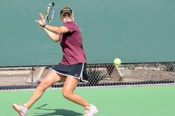 ASU women's tennis player swinging racket at ball
