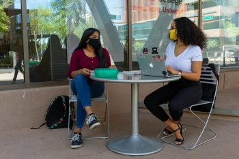 Two women at a table outside wearing masks on ASU's campus
