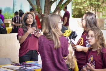Women talk at a table at an ASU early outreach event on the Tempe campus