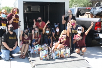 ASU Moms in masks giving forks up in front of a truck with care packages