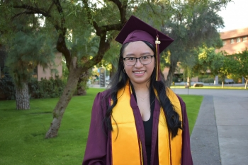 Fall 2020 graduate Monica Orillo poses in her maroon and gold graduation regalia, including a gown, stole, and mortarboard. A tree and grassy lawn are in the background.