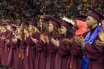 Students in maroon caps and gowns clap