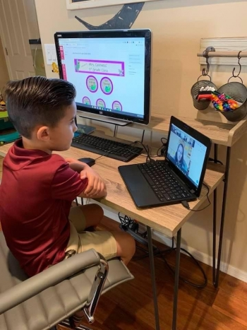 Child using computers to learn online at home