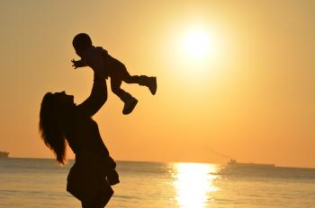 Woman holding child up by a water sunset