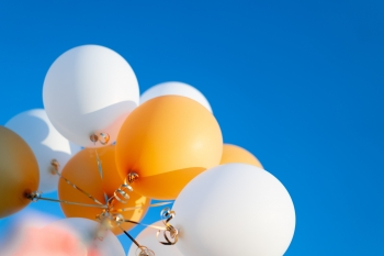 Gold and white balloons against a blue sky.