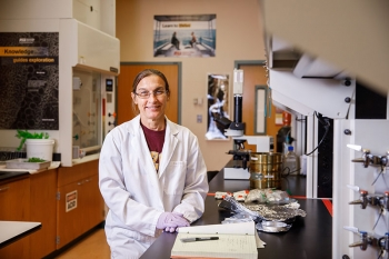 A woman stands in a laboratory, surrounded by scientific equipment. The caption reads: Beth Polidoro is a marine biologist who leads ASU's Salt Water Assessment Team (SWAT) lab, and an associate professor of environmental chemistry and aquatic conservatio