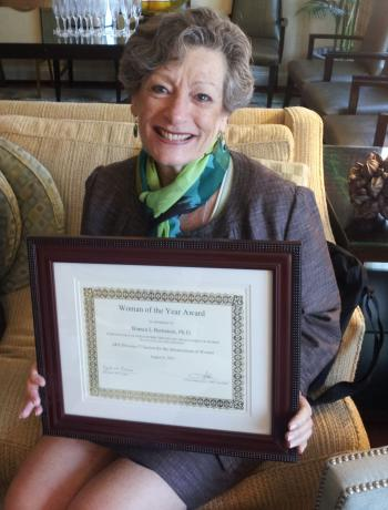 woman holding a framed certificate