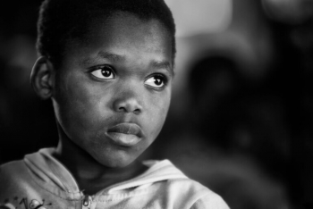 Black and white image of the face of a young Black child