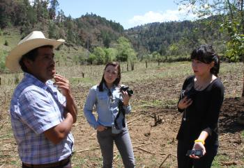 journalism students talking to a farmer in a field