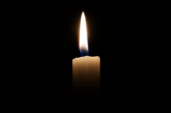 A tall flame burns atop a thin white candle against a black background.