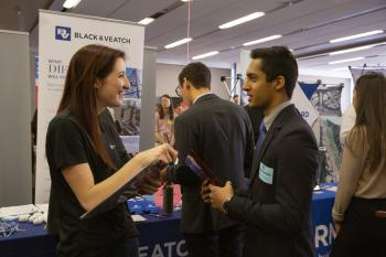 student talking to an employer at a career fair