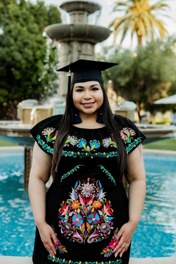 Carolina Tovar in her graduation cap in front of the Old Main fountain at ASU's Tempe campus