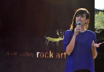 Casandra Hernandez speaking into microphone at Deer Valley Rock Art Center