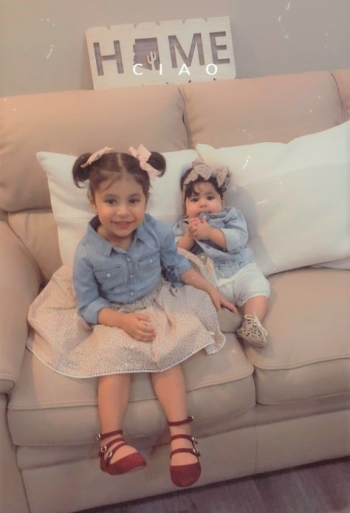 The children of Rayya Aljarallah pose on her couch.