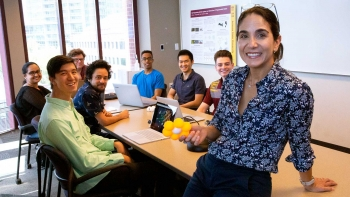 Professor Andréa Richa and her lab group students gathered around a table