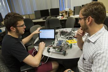 two ASU engineering students talking with a robot on a table