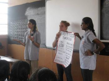women stand and lecture at the front of a classroom