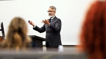 man wearing see through mask speaking to class