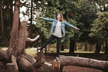 Courtney Baxter stands on a log