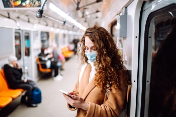 Woman wearing a mask checks her phone while riding public transportation