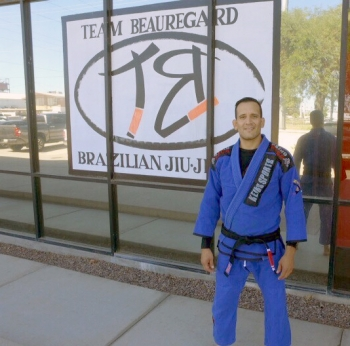 Graduating ASU doctoral student Cristian Lopez Villegas stands outside a martial arts studio. / Photo by Josh Morris.