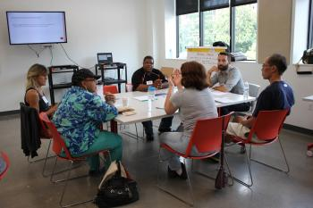Local community members talk around table about driver-less cars