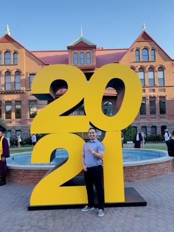 ASU grad Daniel Sanchez in front of a big 2021 statue at Old Main on ASU's Tempe campus
