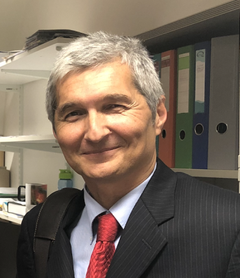 ASU Professor Danko Šipka stands in his office on campus. He has silvery hair and broad smile, but isn't showing teeth. He is wearing a pale blue dress shirt, red tie and black suit coat.