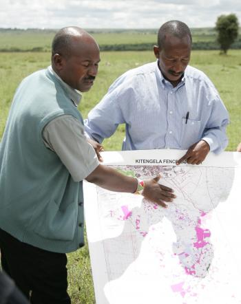 Two African community members holding a map.