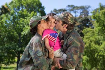 Picture of couple in military clothes holding and kissing their young child.