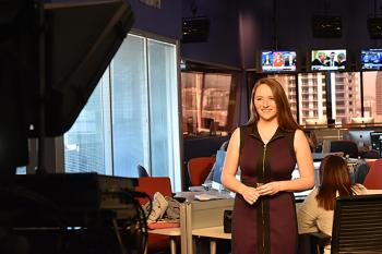 student in front of broadcast camera in newsroom