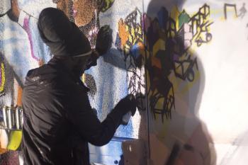 Graffiti artist works on mural