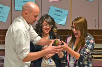 A graduate student mentor hands a live bullfrog to a middle school student.