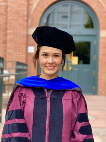 Fall 2020 doctoral graduate Cindy Bonilla-Cirocco stands in front of an old brick building. She is wearing her graduation regalia, including a maroon and black gown, blue hood, and black cap.