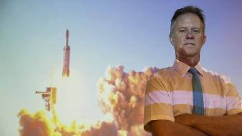 Hugh Barnaby stands in front of a projection of a SpaceX Falcon Heavy rocket launch.