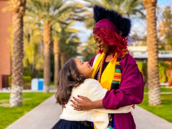 ASU grad Edeline Plaisival in her cap and gown on Palm Walk smiling at her 8-year-old daughter