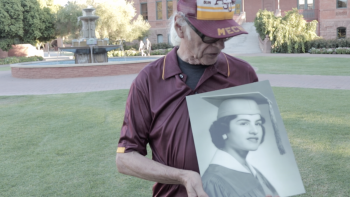 Edward Delci holds a portrait of his late wife, Virginia Pesqueira, in front of Old Main at ASU's Tempe campus