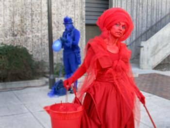Two performers, one clad entirely in red, and another entirely in blue