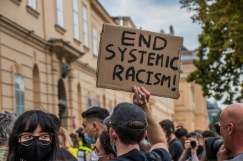 Picture of a protest sign help up that reads end systemic racism!