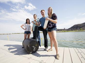 four students on a dock