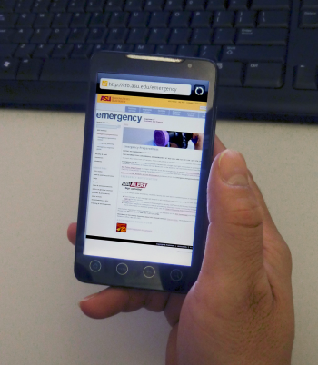 A person is holding a smart phone with the web browser on the ASU emergecny page