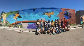 Photo of Facing Immigration II class in front of their mural they helped paint with Hugo Medina