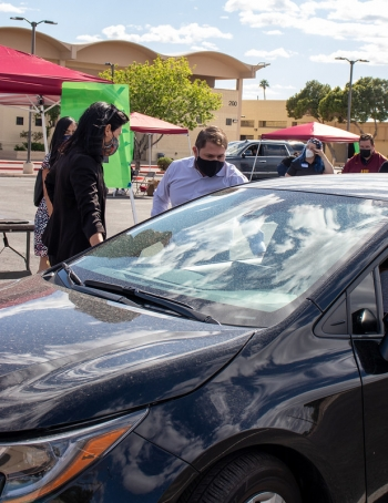 Rep. Ruben Gallego in a mask talking to a passenger in a car
