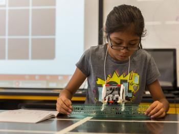 A student tests her LEGO robot at the FIRST LEGO League summer camp.