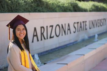Yvonne Cabrera sitting in her graduation cap in front of ASU sign
